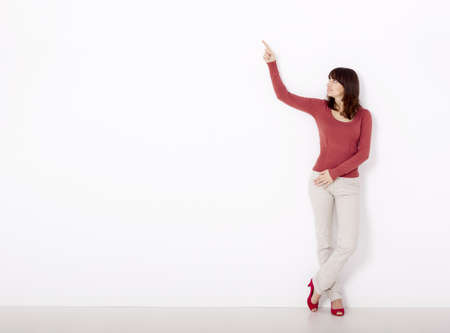 Beautiful young woman pointing to the right side with copyspace, against to a white wall photo