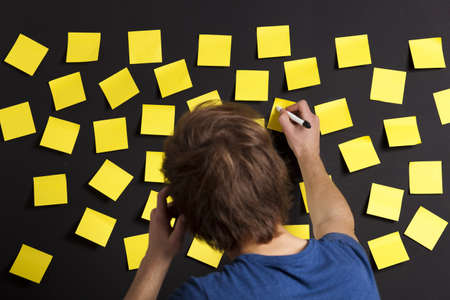Young student writing a message on a yellow note photo
