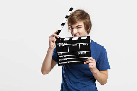 directors cut: Casual young man holding a clapboard, over a gray background
