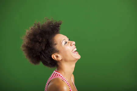 Beautiful African woman laughing over a green background photo