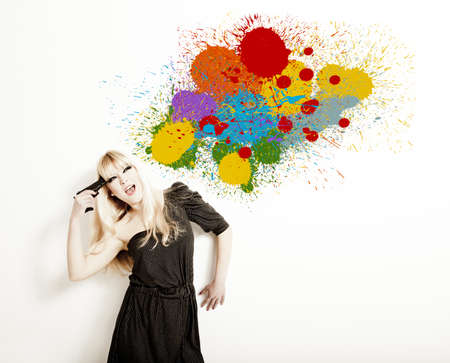 Portrait of a beautiful blonde woman commiting suicide with a splash of paint on the wall photo