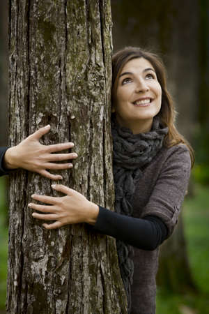 Portrait of a beautiful young woman hugging a tree in fall season photo