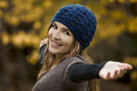 Portrait of a beautiful young woman relaxing with arms open and enjoying the fall season photo