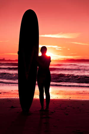 Surfer girl with surfboard at sunset beach photo