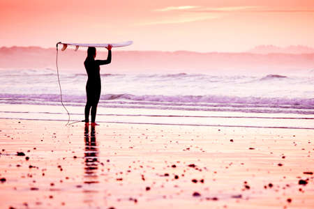 Female surfer on the beach at the sunset photo