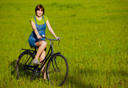 Happy girl with a bicycle in a green meadow photo