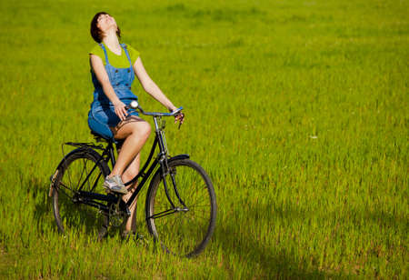 Happy girl over a bicycle and looking the view, in a green meadow Stock Photo - 14902136