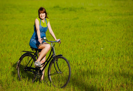 girl on bike: Happy girl with a bicycle in a green meadow