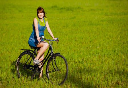 bicicleta retro: Ni�a feliz con una bicicleta en un prado verde