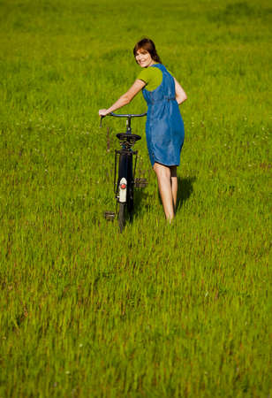 Young woman walking side by side with a bicycle photo