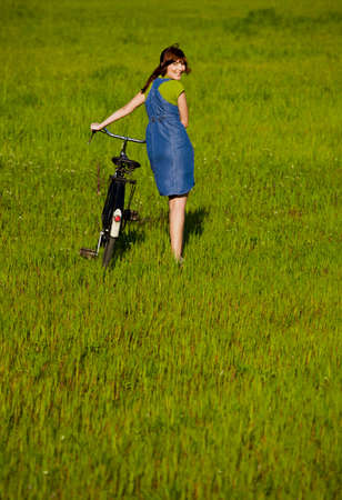 old people walking: Young woman walking side by side with a bicycle Stock Photo