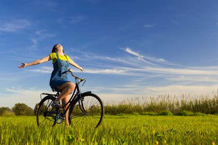 Bonne fille sur un vélo et regarder la vue, dans une verte prairie