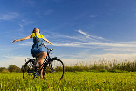 joy health: Happy girl over a bicycle and looking the view, in a green meadow