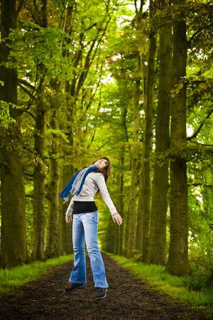 persona saltando: Mujer saltando en hermosa carretera rodeada de árboles grandes