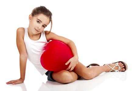 ni�a: Retrato de una ni�a sentada en el suelo y abrazando un globo rojo, aislados en fondo blanco
