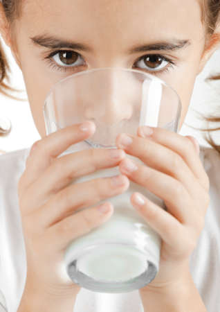 Portrait of a little girl drinking a cup of milk photo