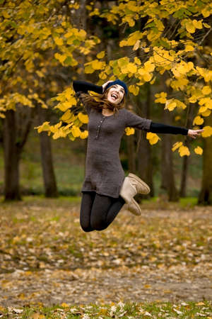 Beautiful and happy woman jumping in a autumn day Stock Photo - 15264705