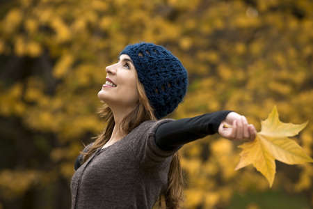 Portrait of a beautiful young woman relaxing with arms open and enjoying the fall season Stock Photo