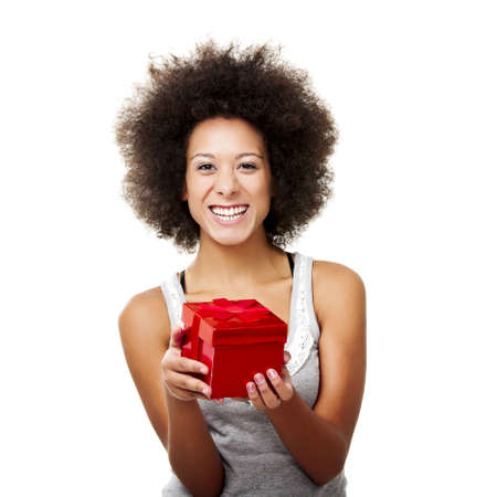 adult birthday: Beautiful happy young woman holding a red christmas gift, isolated on white
