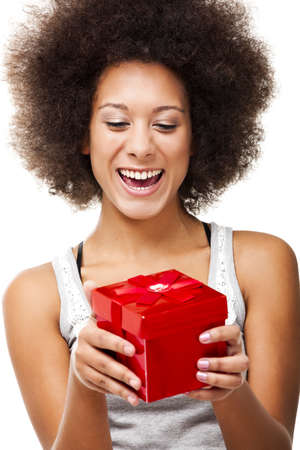 Beautiful happy young woman holding a red christmas gift, isolated on white photo