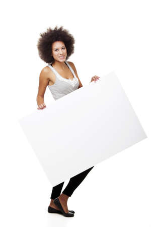 Beautiful young woman holding and showing a white billboard with copy space, isolated on white  Stock Photo - 15264684