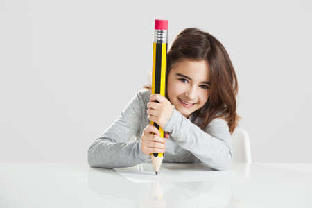 Beautiful little girl in a desk playing with a big pencil, against a gray background photo