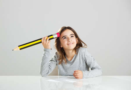 Beautiful little girl in a desk playing with a big pencil, against a gray background Stock Photo - 15264694