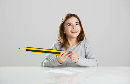 Beautiful little girl in a desk playing with a big pencil, against a gray background Stock Photo - 15290937