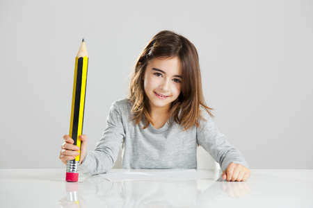 Beautiful little girl in a desk playing with a big pencil, against a gray background Stock Photo - 15264692