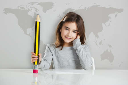 Beautiful little girl in a desk playing with a big pencil, against a gray background