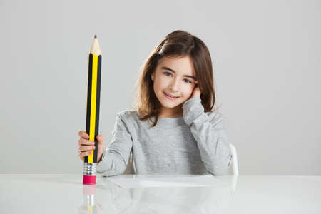 Beautiful little girl in a desk playing with a big pencil, against a gray background Stock Photo - 15264723