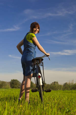 Happy girl over a bicycle and looking back, in a green meadow photo