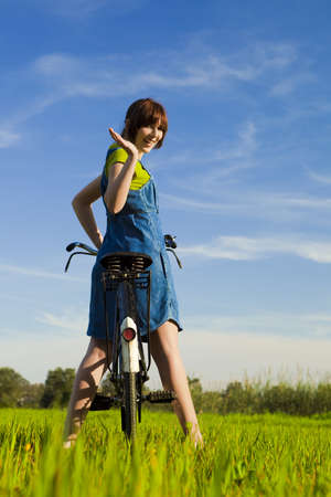 Happy girl over a bicycle and looking back and saying goodbye, in a green meadow