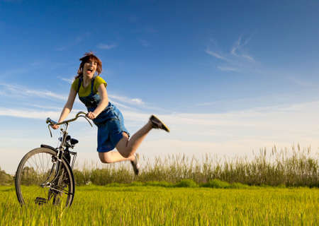 Mujer feliz con una bicicleta vieja en un prado verde y saltando