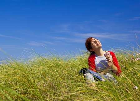 Happy woman sitting on a green meadow and holding flowers Stock Photo - 15760656