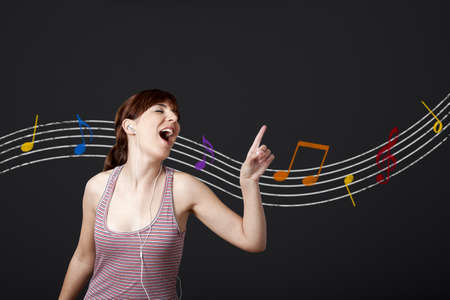 Happy young woman listen music and dancing, with musical notes in the background photo