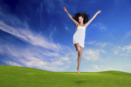 Happy girl jumping in a beautiful green meadow Stock Photo - 15760523