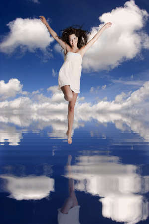 Beautiful and happy girl jumping over the water with her reflection photo
