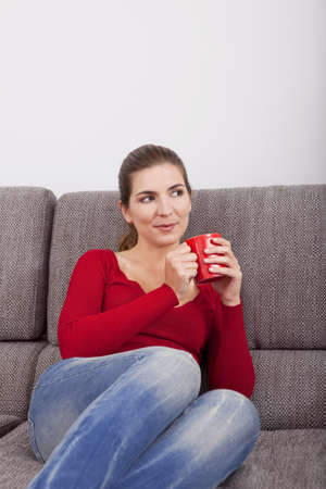 Beautiful woman resting on the sofa and drinking coffee Stock Photo - 15760645