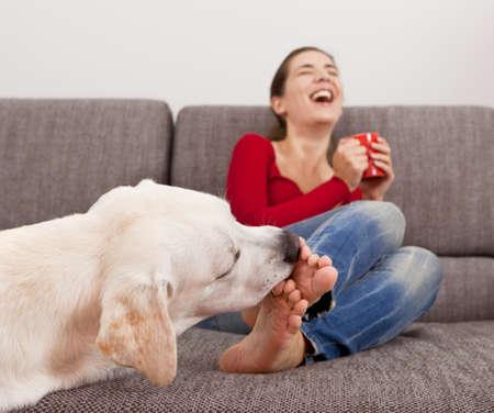 mujer tomando cafe: Mujer bebiendo café en el sofá con su perro lamiéndose los dedos de los pies