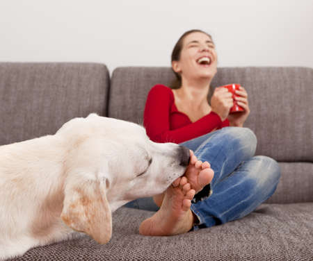 Woman drinking coffee on the sofa with her dog licking her toes Stock Photo