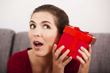 guessing: Beautiful and happy woman trying to guess what is inside the christmas present