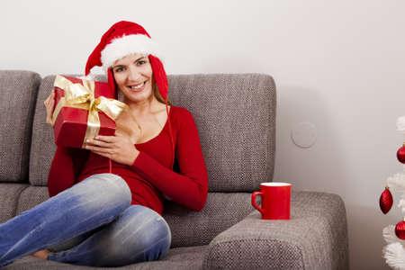 Mulher bonita que senta-se no sofá com um presente e vestindo um chapéu de Santa Banco de Imagens - 15760575