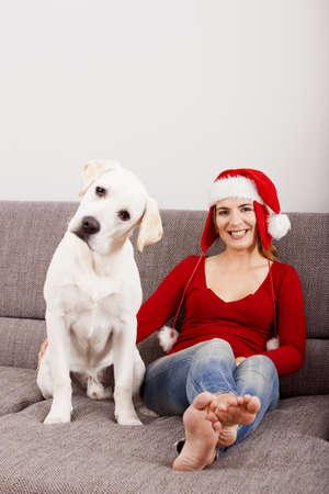 Kadın köpek ile koltukta oturan ve bir Santa şapka giyiyor Stok Fotoğraf - 15760633