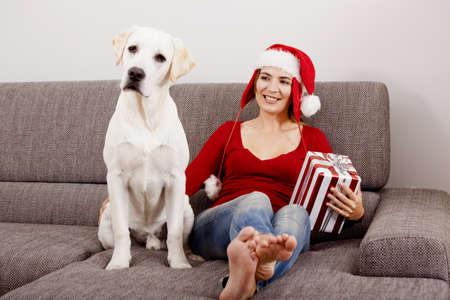 Woman sitting on the sofa with her dog and wearing a santa hat   Stock Photo - 15760655