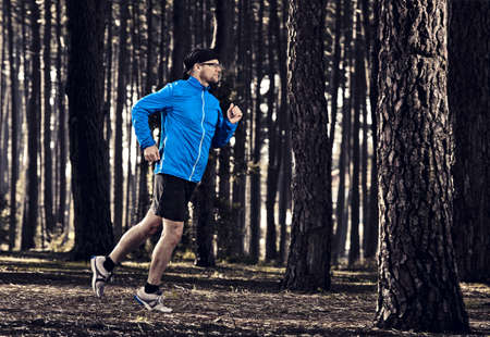 Athletic man doing exercise, running in the forest Stock Photo - 16126456
