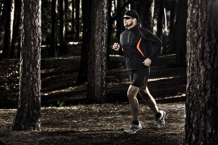 Athletic man doing exercise, running in the forest photo
