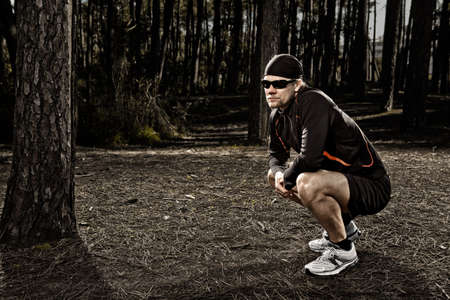 Athletic man resting after running in the forest Stock Photo - 16126458
