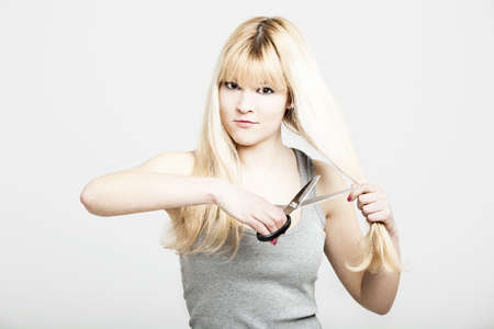 Portrait of a young and beautiful blonde cutting her own hair Stock Photo - 16126432