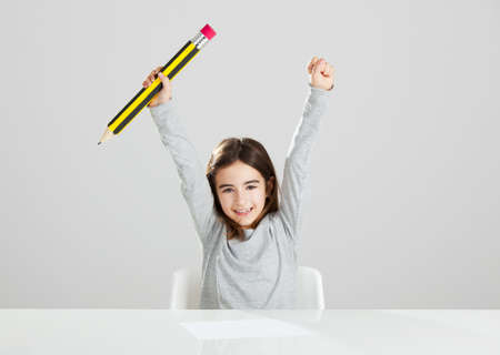 Beautiful little girl in a desk playing with a big pencil, against a gray background Stock Photo - 16126417
